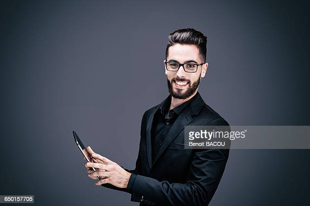 Portrait of a smiling young businessman holding a touch pad in his hands