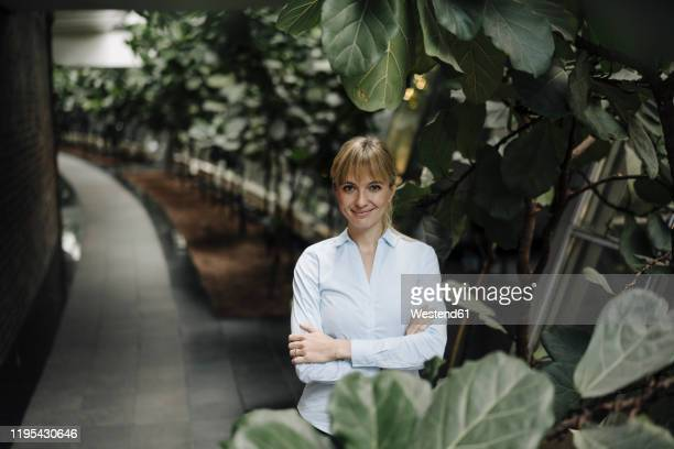 portrait of a smiling young businesswoman in a modern office building surrounded by plants - umgeben stock-fotos und bilder