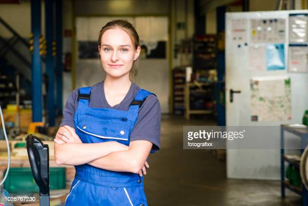 Portrait of a smiling young female trainee in metal industry, arms crossed