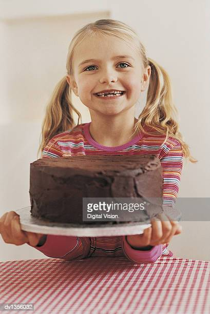 Portrait of a Smiling, Young Girl Holding a Chocolate Cake on a Plate Over a Checked Tablecloth