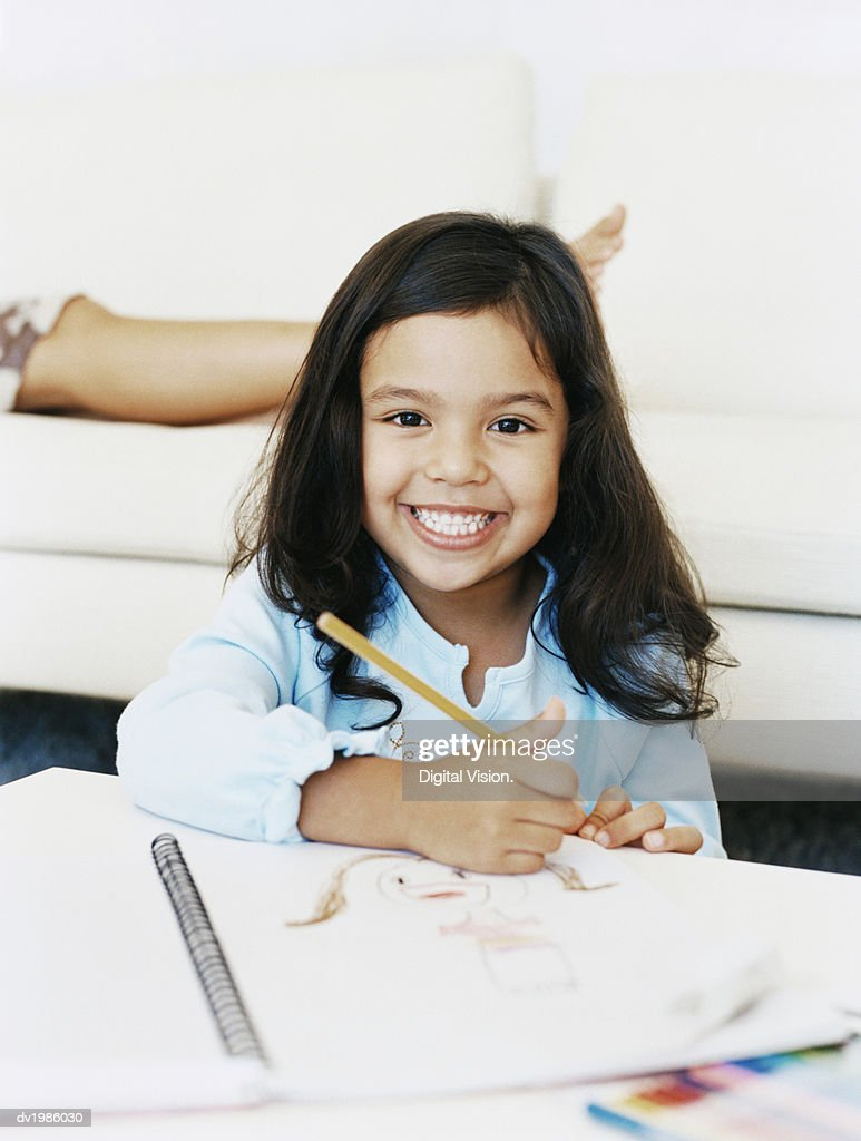 Portrait of a Smiling, Young Girl With a Drawing Book at a Table : Stock Photo