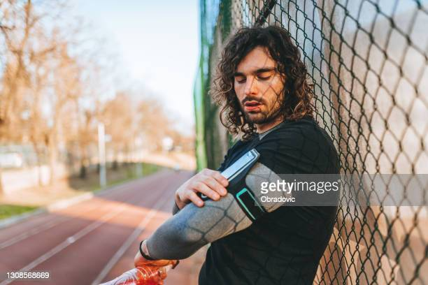 portrait of a smiling young man in sports wear with headphones and portable information devices resting at a white stone wall, with copy space. - portable information device imagens e fotografias de stock