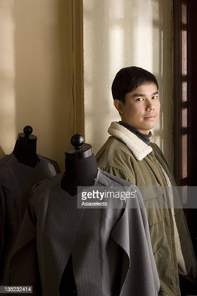 Portrait of a smiling young man standing by mannequins