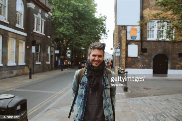 portrait of a smiling young man, walking in london, shoreditch - double denim stock photos and pictures
