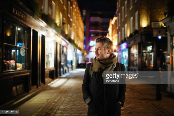 portrait of a smiling young man, walking in london, shoreditch - multi colored coat stock photos and pictures