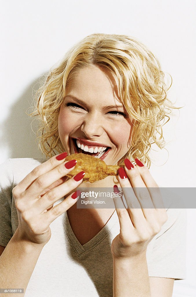 Portrait of a Smiling, Young Woman Eating a Deep Fried Chicken Drumstick : Stock Photo
