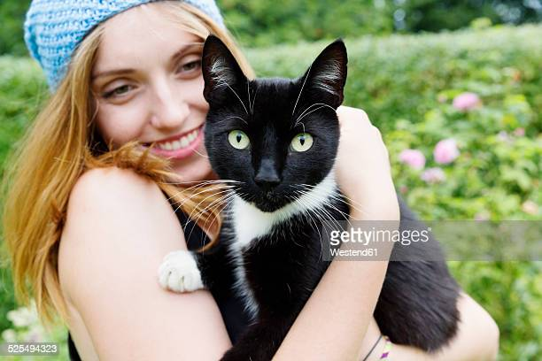 portrait of a smiling young woman holding cat on her arms - female hairy arms stock photos and pictures