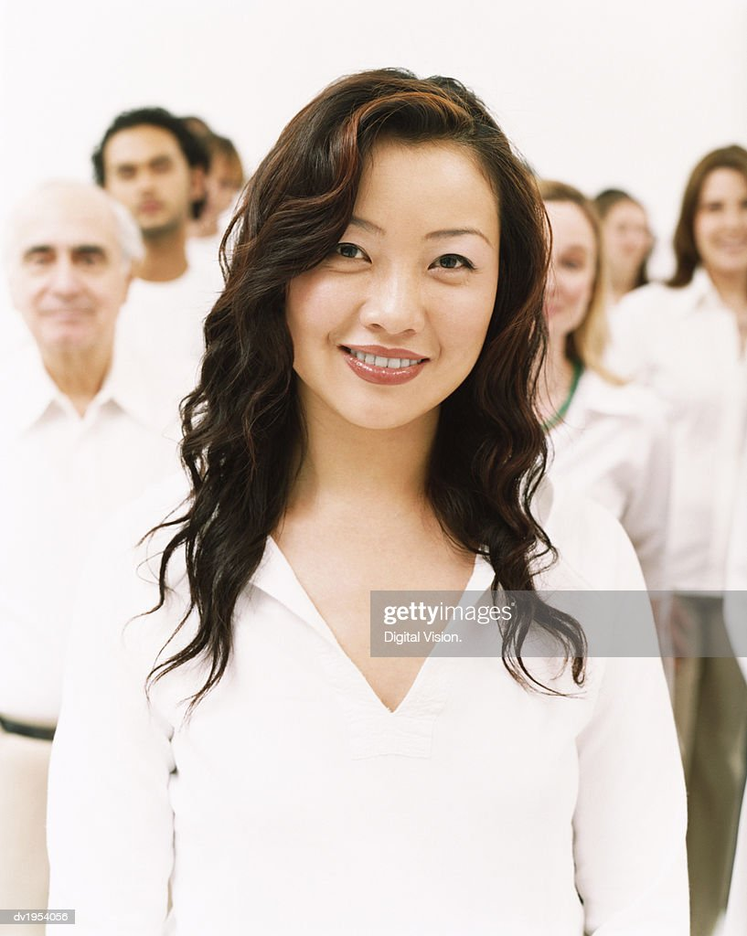 Portrait of a Smiling Young Woman in a White Top Standing in Front of a Crowd : Stock Photo