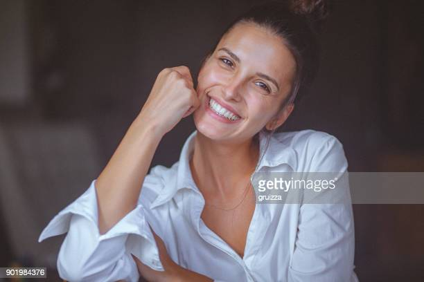 Portrait of a smiling young woman in white shirt