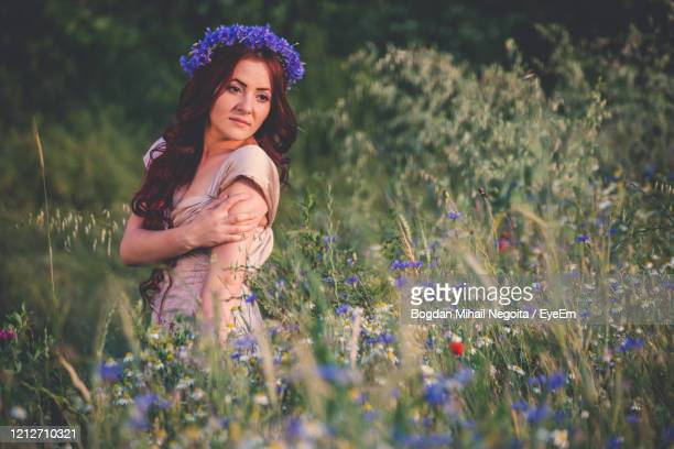 portrait of a smiling young woman on field - bogdan negoita stock pictures, royalty-free photos & images
