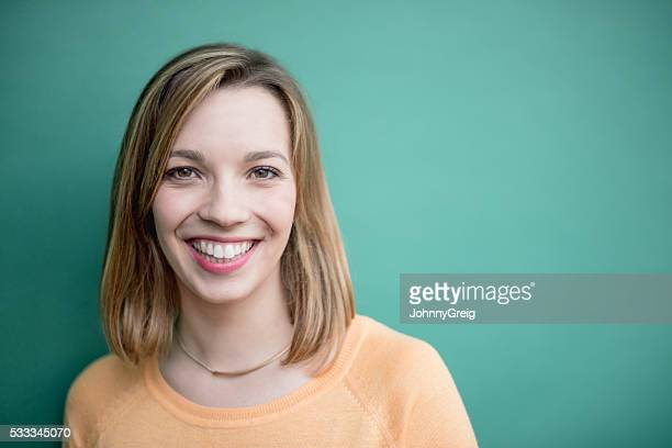 Portrait of a smiling young woman on green