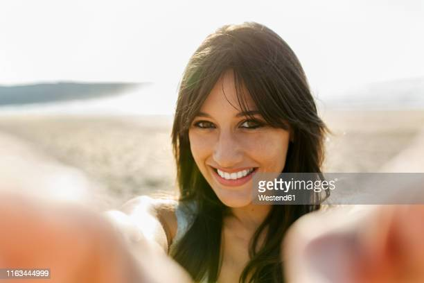 portrait of a smiling young woman on the beach - 30 34 anos imagens e fotografias de stock