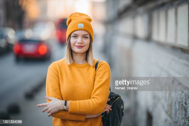portrait of a smiling young woman on the street - top garment stock pictures, royalty-free photos & images