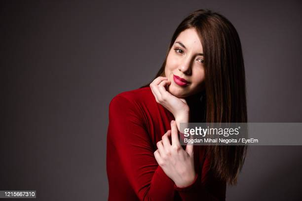 portrait of a smiling young woman over black background - bogdan negoita stock pictures, royalty-free photos & images