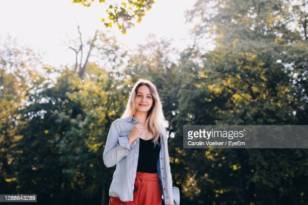 portrait of a smiling young woman standing against trees - one mid adult woman only stock pictures, royalty-free photos & images