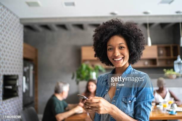 retrato de uma mulher nova de sorriso que usa o telemóvel - só uma mulher - fotografias e filmes do acervo