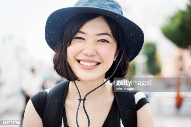 portrait of a smiling young woman wearing a hat. - 20代 ストックフォトと画像