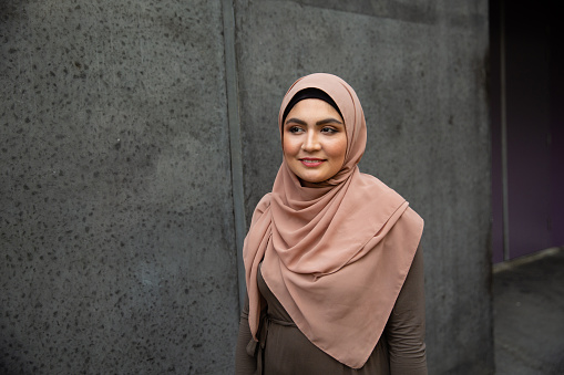 Portrait of a smiling young woman wearing hijab on street - gettyimageskorea