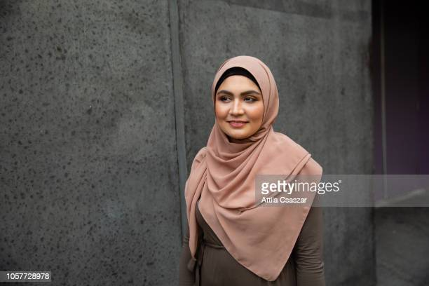 portrait of a smiling young woman wearing hijab on street - image stock pictures, royalty-free photos & images