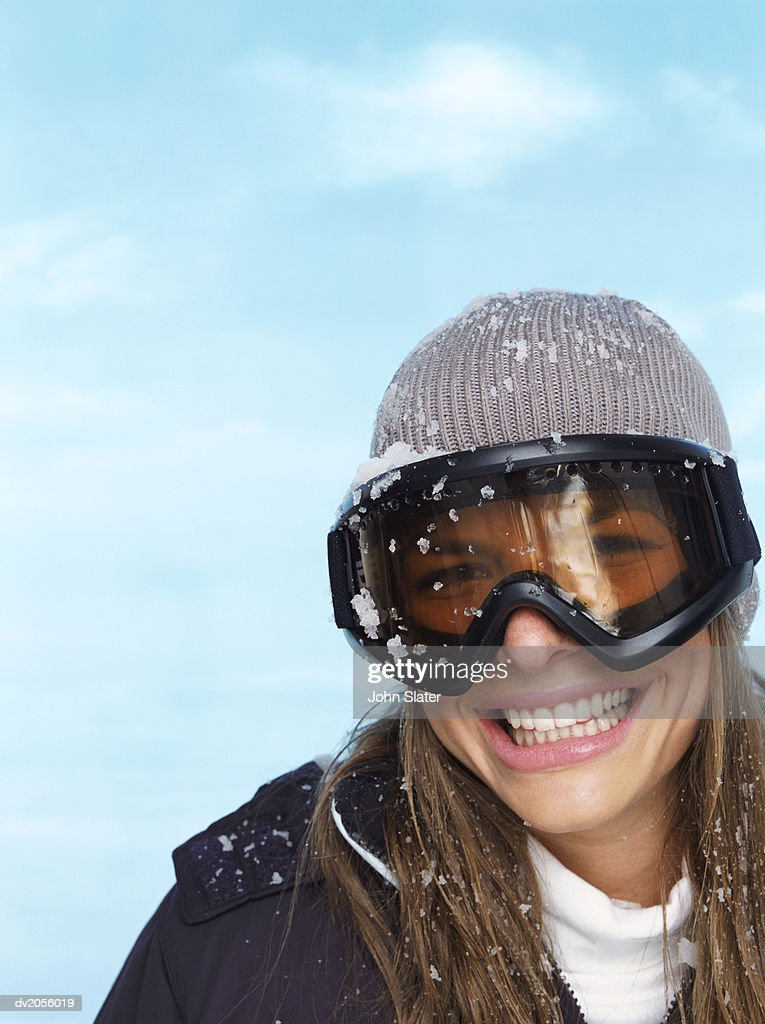 Portrait of a Smiling Young Woman Wearing Snow Covered Ski Goggles : Stock Photo