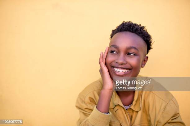 Portrait of a smiling young woman wearing yellow jacket in front of yellow wall