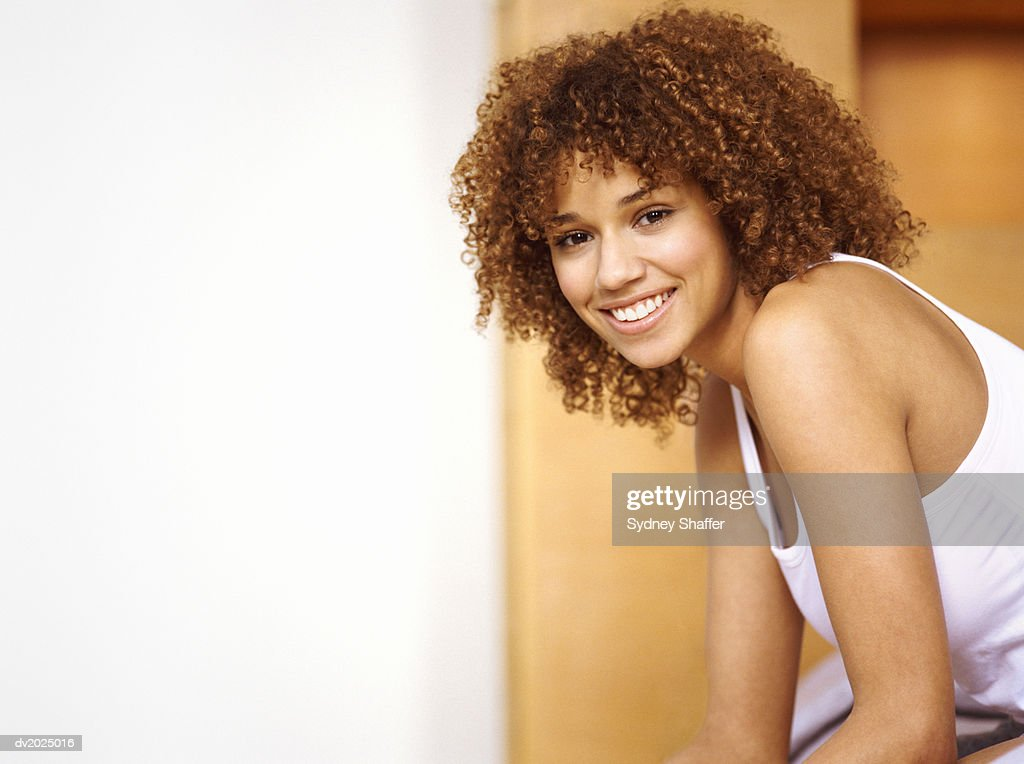 Portrait of a Smiling Young Woman With Curly Brown Hair : Stock Photo