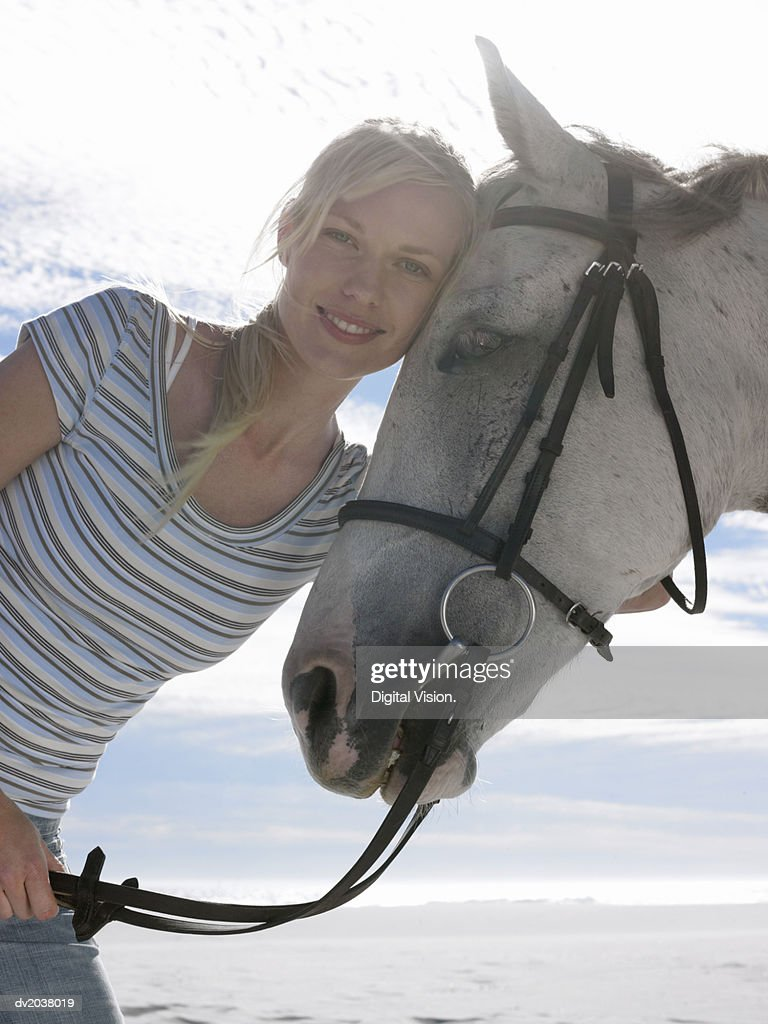 Portrait of a Smiling, Young Woman With Her Horse : Stock Photo