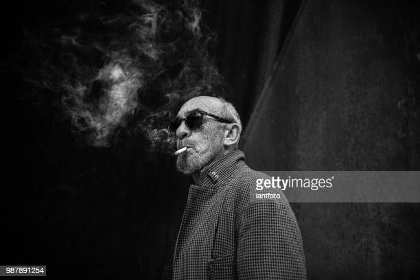 portrait of a smoking man. - desaturated stock pictures, royalty-free photos & images
