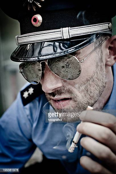portrait of a smoking policeman in blue uniform with sunglasses