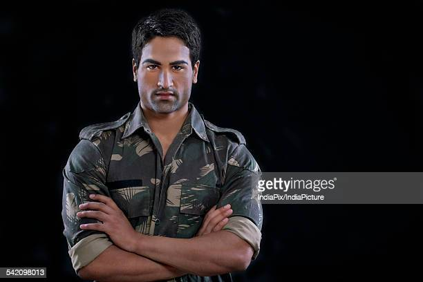 portrait of a soldier standing with his arms crossed - indian soldier stock photos and pictures