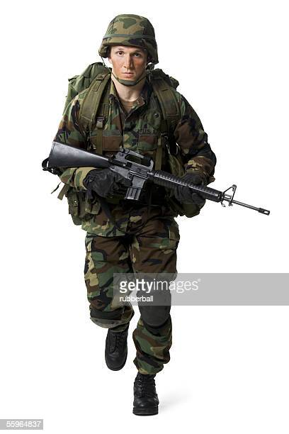 portrait of a soldier walking with a rifle - boots rifle helmet stock pictures, royalty-free photos & images