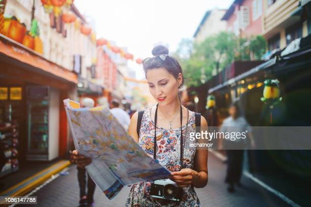 Portrait of a solo traveler woman in Singapore checking the map