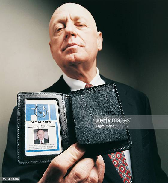 portrait of a special agent showing his id card - fbi id stock pictures, royalty-free photos & images