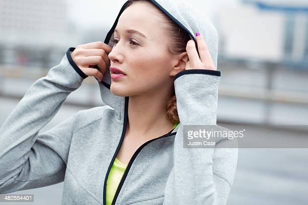 Portrait of a sporty woman taking her hood off