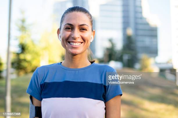 portrait of a sporty young woman exercising outdoors. - hair back stock pictures, royalty-free photos & images