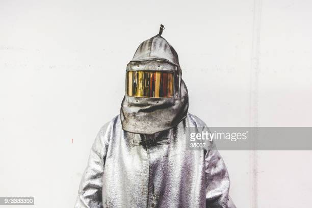 portrait of a steel worker in a silver suit with a fire mask
