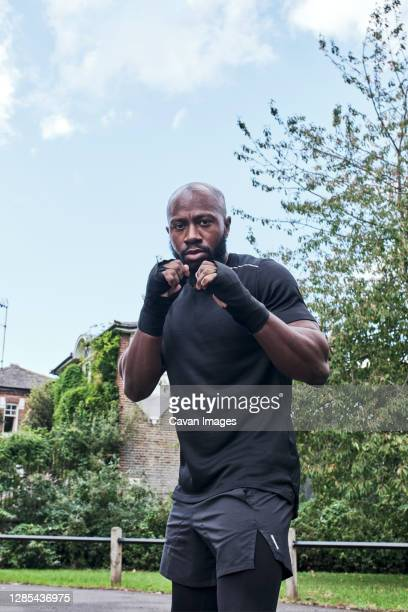 portrait of a strong man in boxing position with bandages on his hands. - boxing stock pictures, royalty-free photos & images