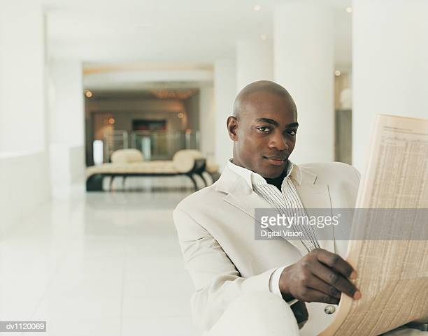 Portrait of a Stylish Businessman Sitting in a Hotel Lobby Holding a Newspaper