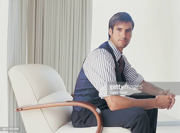 Portrait of a Stylish Businessman Sitting in an Armchair
