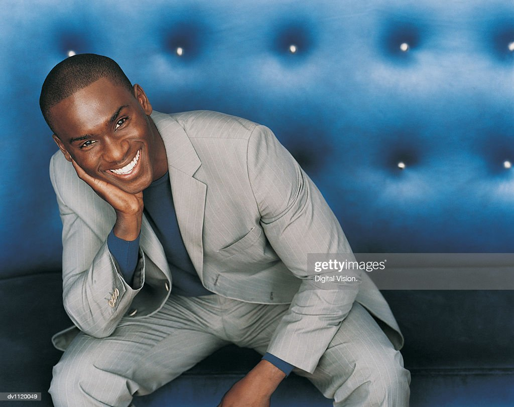 Portrait of a Stylish Businessman Sitting on a Blue Seat : Stockfoto