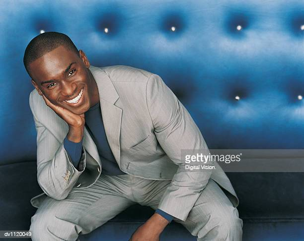 Portrait of a Stylish Businessman Sitting on a Blue Seat