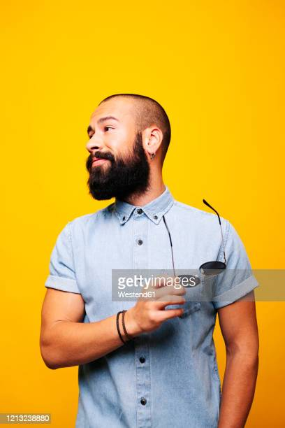 portrait of a stylish young man in studio with sunglasses - short sleeved stock pictures, royalty-free photos & images