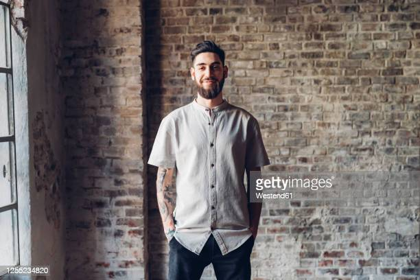 portrait of a stylish young man standing in loft - short sleeved stock pictures, royalty-free photos & images