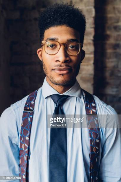 portrait of a stylish young man wearing shirt, tie and suspenders - サスペンダー ストックフォトと画像