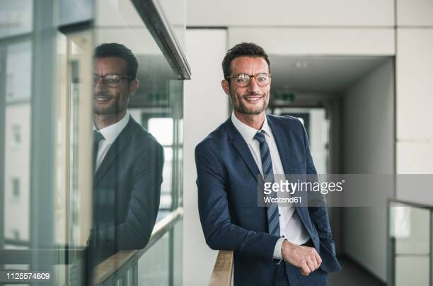 portrait of a successful businessman, standing in office building - krawatte stock-fotos und bilder