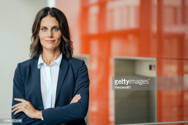 portrait of a successful businesswoman, standing in front of elevator, with arms crossed - anzug stock-fotos und bilder