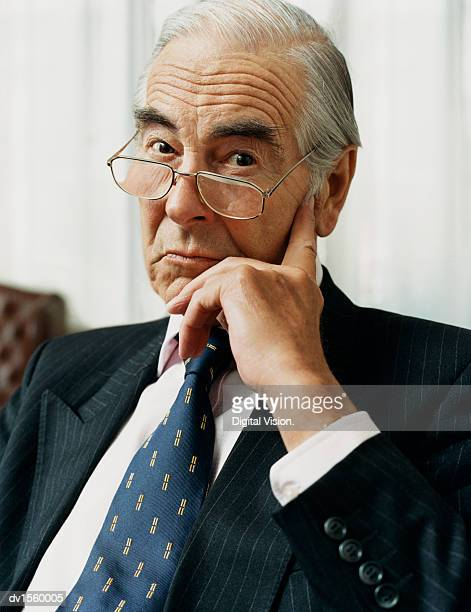 portrait of a sulking businessman wearing spectacles and a pinstripe suit - striped suit stock photos and pictures