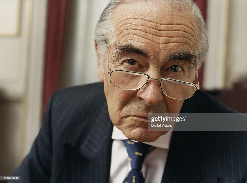 Portrait of a Sulking Businessman Wearing Spectacles and a Pinstripe Suit : Foto de stock