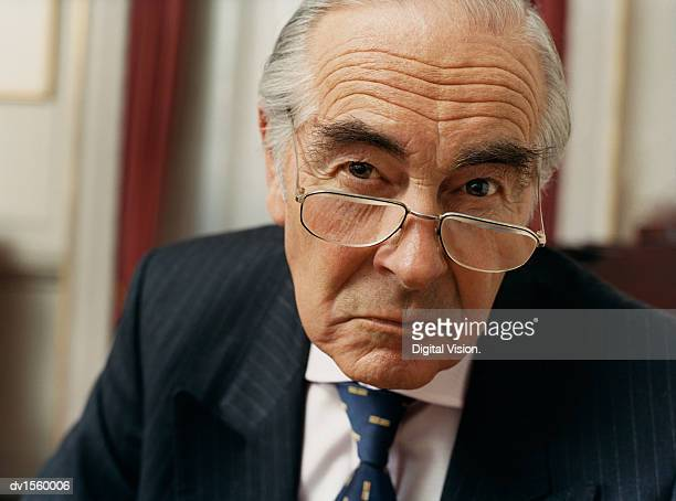 portrait of a sulking businessman wearing spectacles and a pinstripe suit - misnoegd stockfoto's en -beelden
