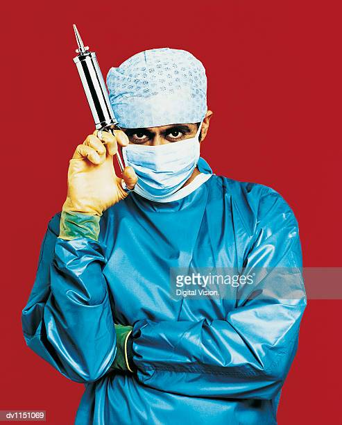 Portrait of a Surgeon in Surgical Scrubs Holding a Syringe